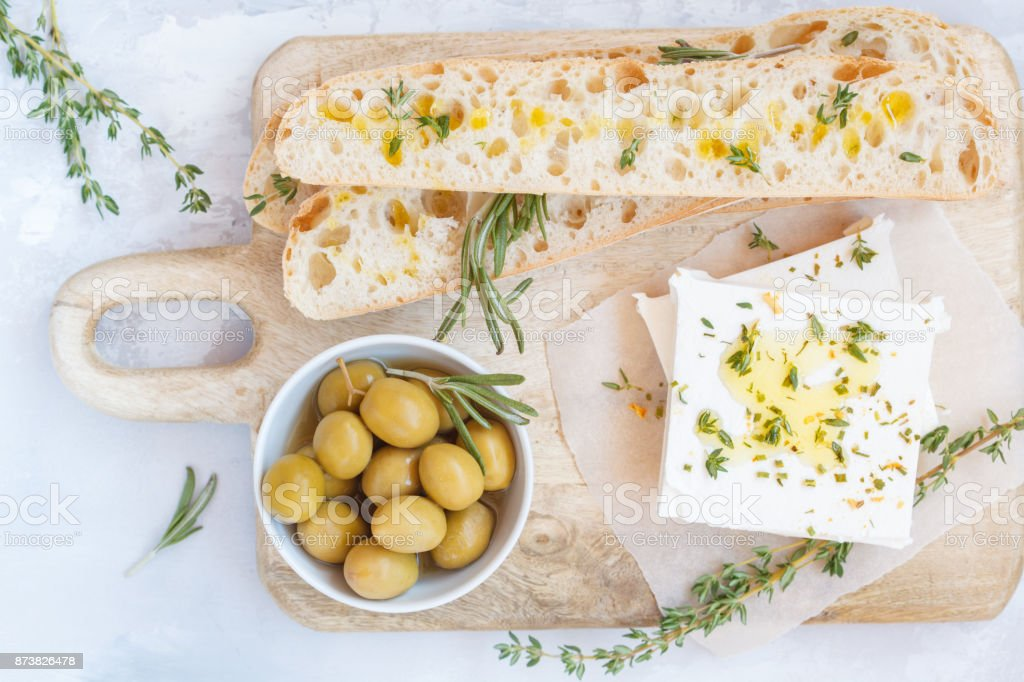 Green olives, feta cheese and fresh ciabata on a wooden board stock photo