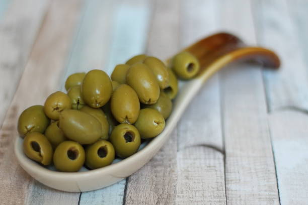 Green olives in bowl on table stock photo