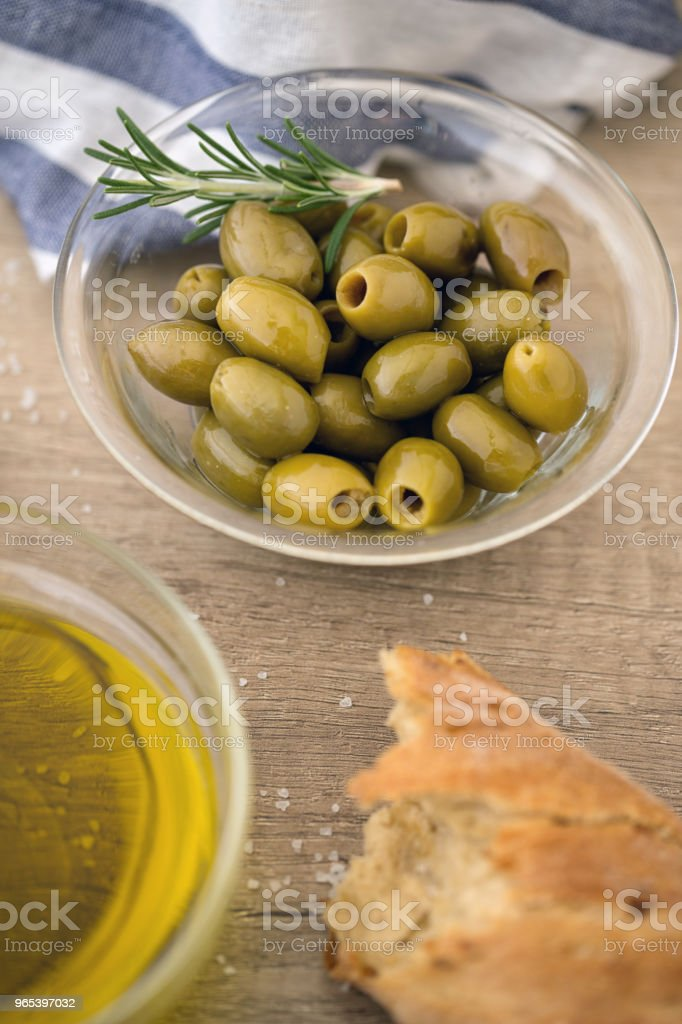 Green olives in the bowl with fresh rosemary served for snack royalty-free stock photo