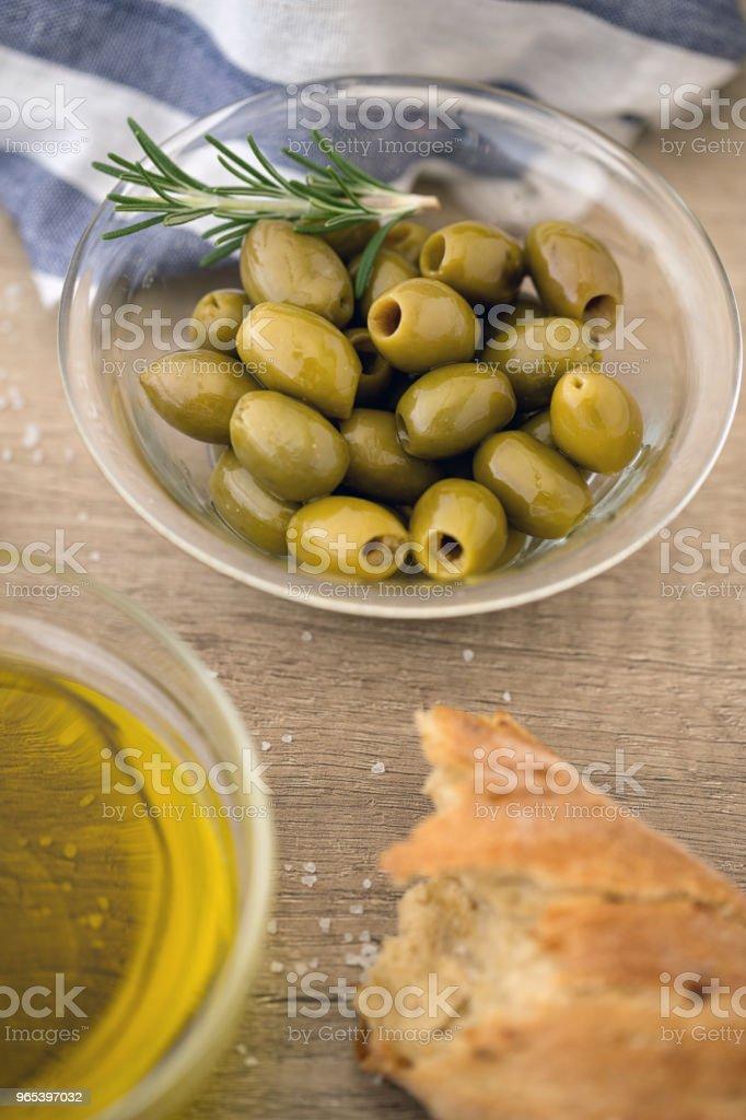 Olives vertes dans le bol avec le romarin frais servi pour collation - Photo de Agriculture libre de droits