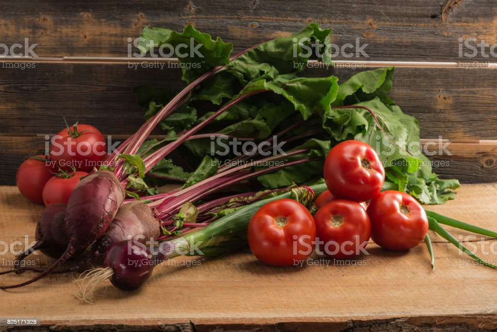 Green onions, beet and tomatoes against the background of old grey boards стоковое фото