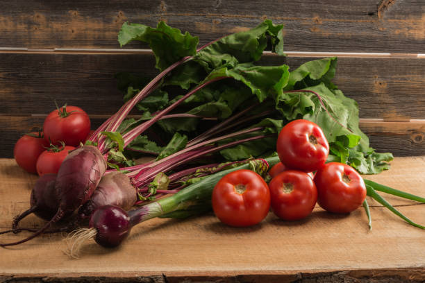 Cтоковое фото Green onions, beet and tomatoes against the background of old grey boards