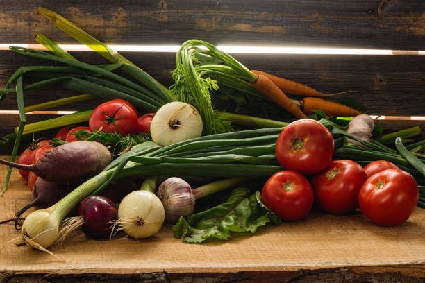 Cтоковое фото Green onions, garlic, carrots, beet and tomatoes against the background of old grey boards