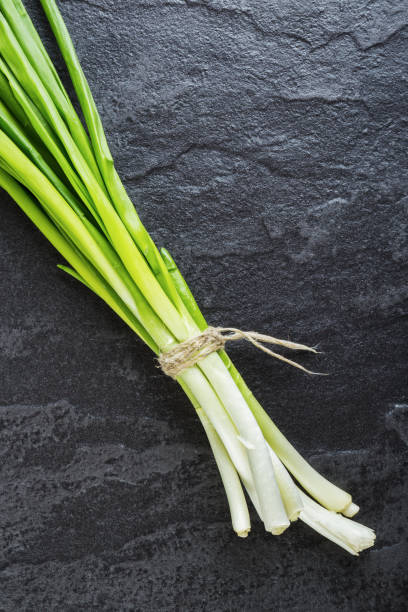 Green onions on a black stone table stock photo