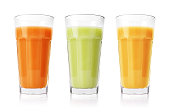 Green, orange and yellow smoothies in glasses isolated on white background