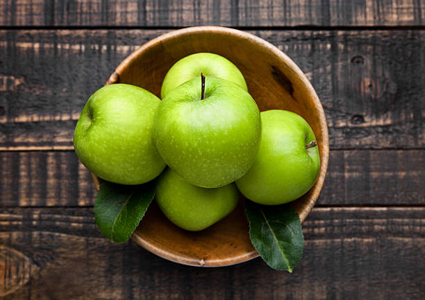 Green organic healthy apples in bowl on wooden board - foto de stock