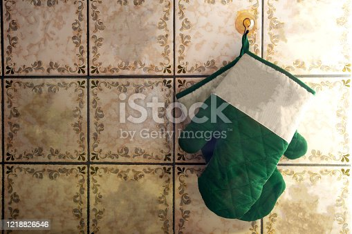 839034546 istock photo Green oven mitts hang on old-fashioned wall with pattern tiles antique design 1218826546