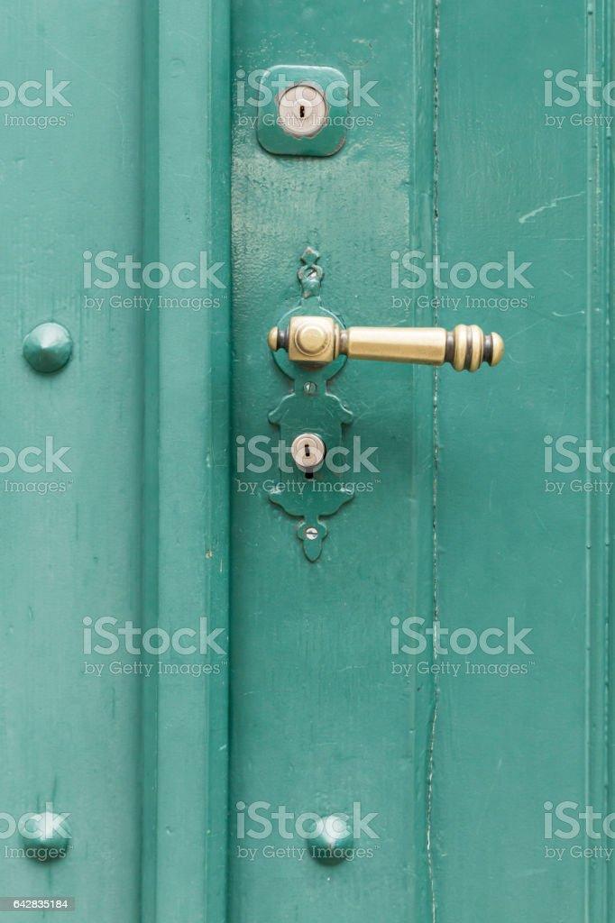 Green painted wooden door with straight golden knob stock photo