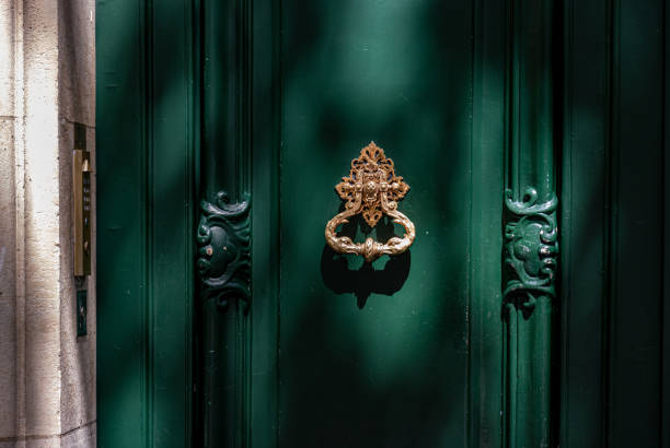 Green painted wooden framed door with gorgeous antique ornate knocker and carving sculptural details. Architectural features of Paris door in bright sunlight with shadows at old building in France. stock photo