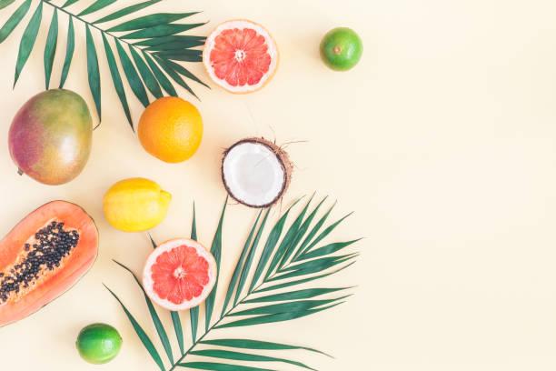 yeşil palmiye yaprakları ve tropikal meyve. düz yatıyordu, en iyi görünümü - hindistan cevizi tropik meyve stok fotoğraflar ve resimler