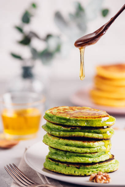 Green pancakes with matcha tea or spinach, dressed honey and red grapes. Healthy breakfast with superfoods. Light background, hugge scandinavian style stock photo
