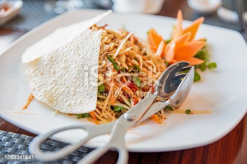 Green Papaya Salad Som tum Thai with silver serving kitchen tongs for picking food.