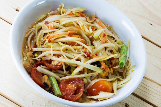 grüner papaya-salat thai-food-stil auf holz hintergrund. - englischer erbsen salat stock-fotos und bilder