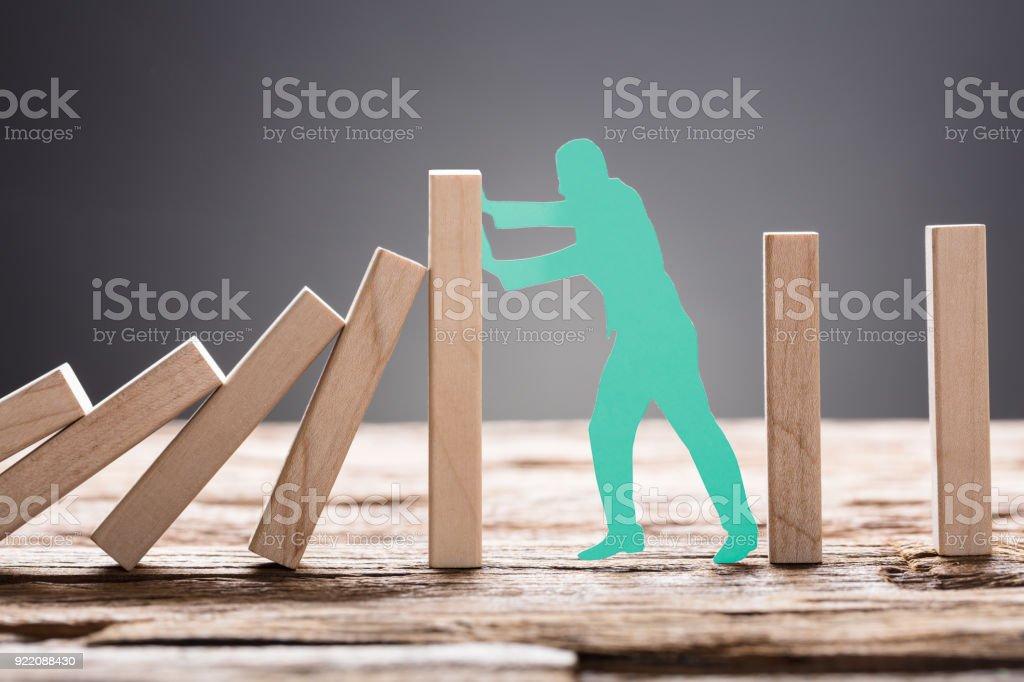 Green Paper Man Stopping Wooden Domino Blocks stock photo