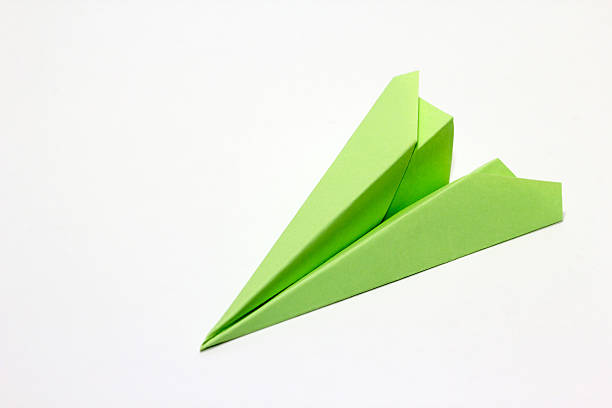 green paper plane - paper airplane stock photos and pictures