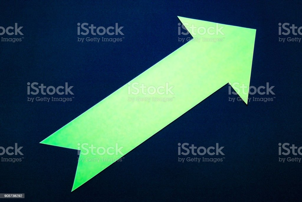 Green paper right arrow on dark blue background. stock photo