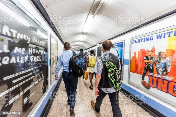 London, UK - June 26, 2018: Green Park tube station underground passage transfer tunnel in city with people commuters walking