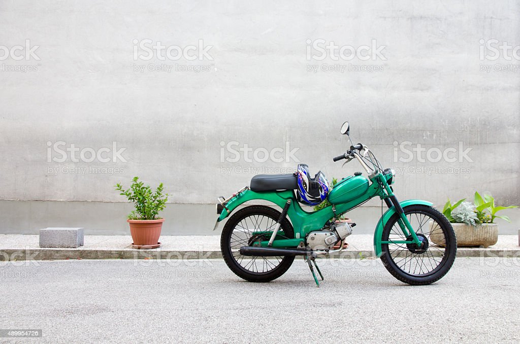 Green parked Moped against Concrete Wall stock photo