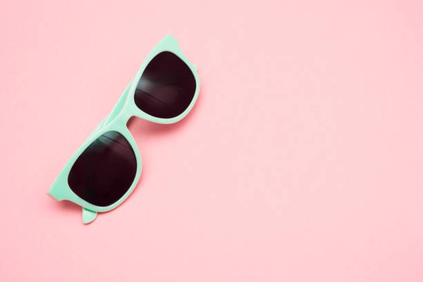 Green pastel sunglasses isolated on punchy pink, top view. Copy space. Summer concept. stock photo