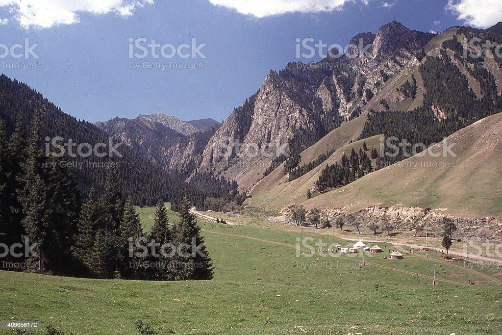 Green pastures Yurts in Valley Tien Shan Mountains Xinjiang China stock photo