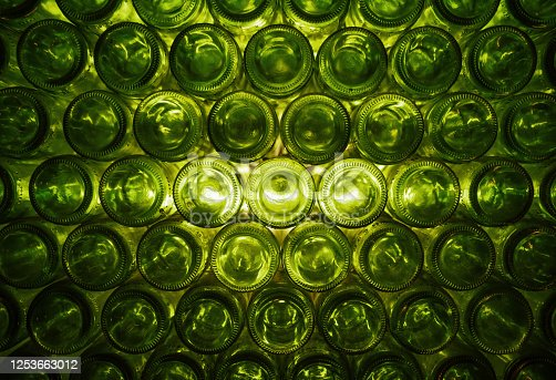 A green pattern / background with back-lit green wine bottles