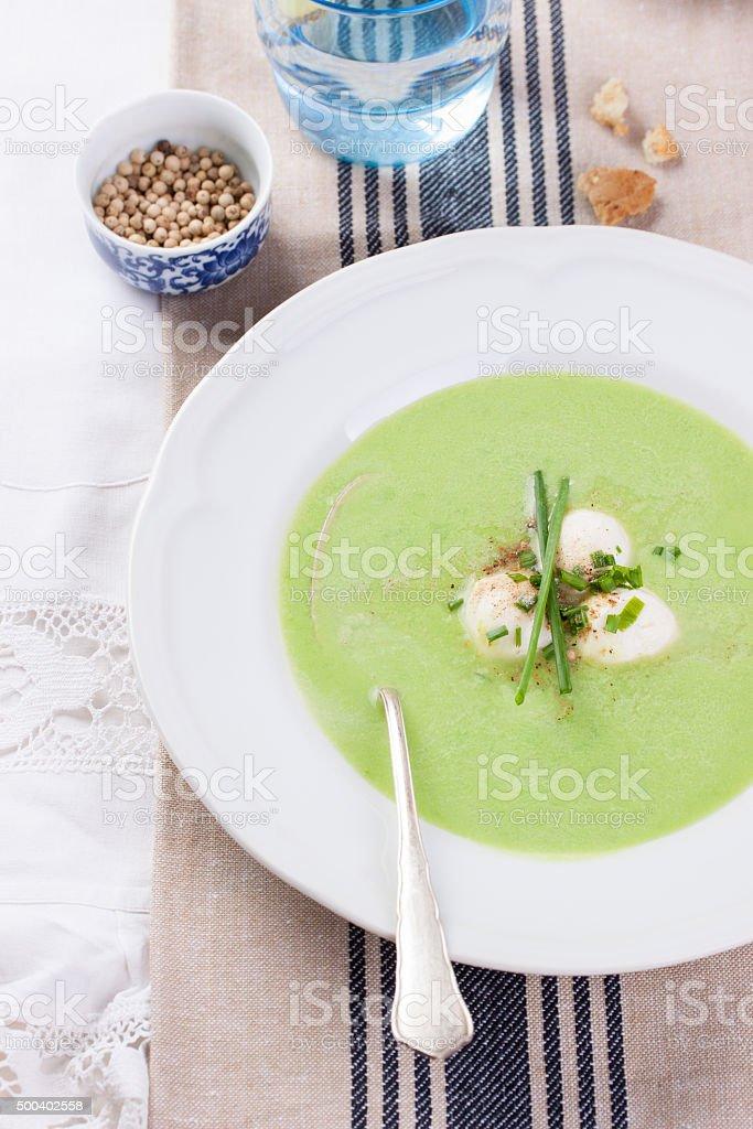 green pea soup with spring onion and mozzarella stock photo