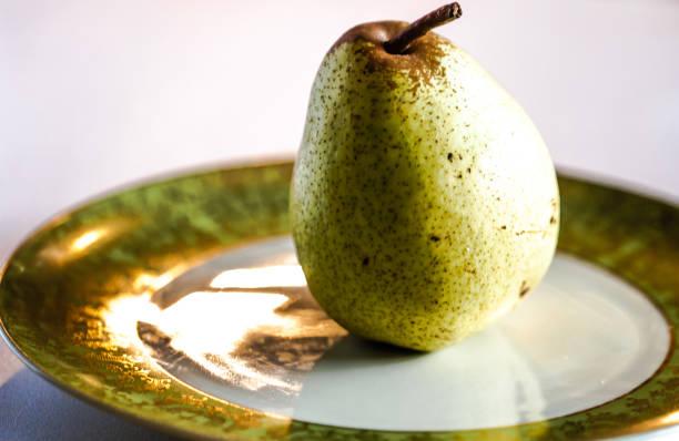 Pera verde no prato de porcelana. Foco seletivo. - foto de acervo