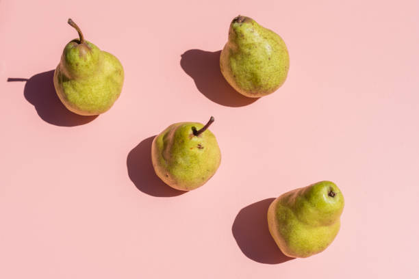 Green pears on pink background from above High angle view of green pears arranged on pink background with hard shadows from bright sunlight (selective focus) still life stock pictures, royalty-free photos & images