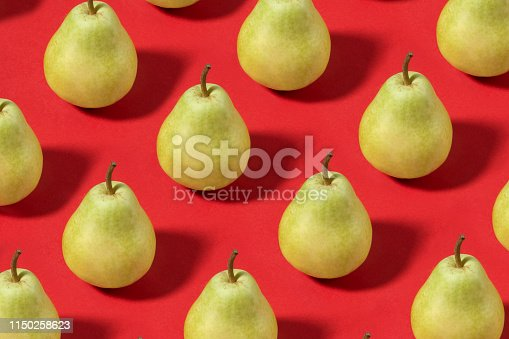 Pears in a row on soft red background