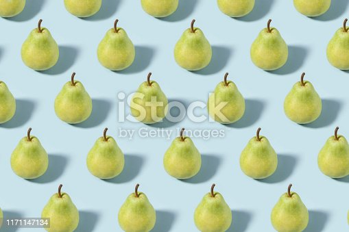 Pears in a row on soft blue background