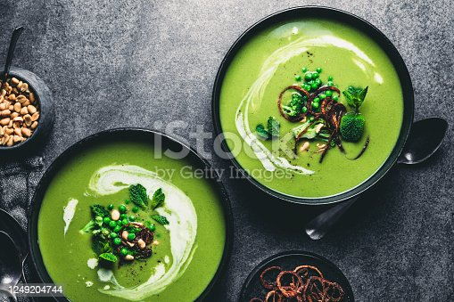 Green peas cream soup in dark plate. Directly above shot of vegetarian green cream soup of green peas with seeds and mint leaves on kitchen counter.
