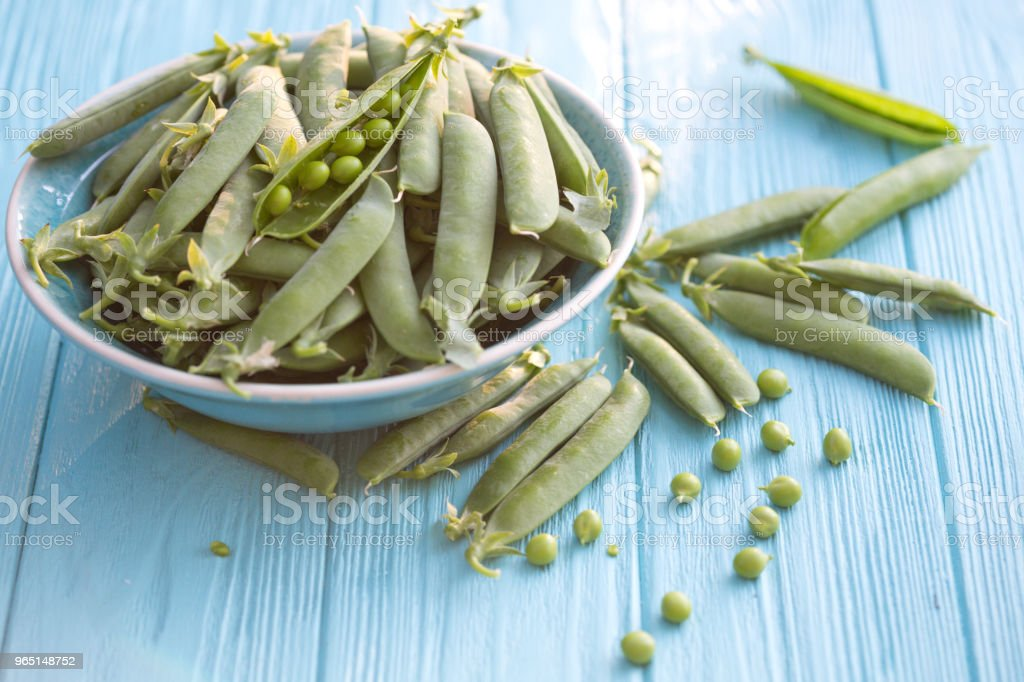 Green peas in pods on a wooden table royalty-free stock photo