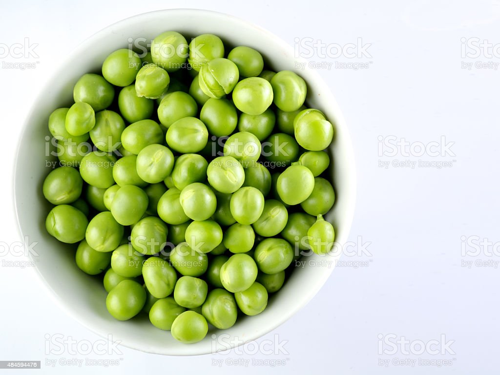 Green peas in the bowl isolated on white stock photo
