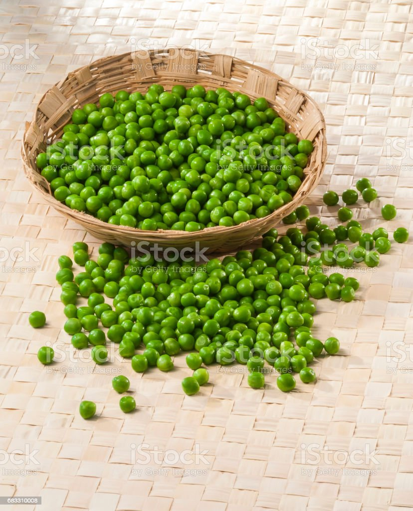 Green Peas in wooden bamboo basket royaltyfri bildbanksbilder