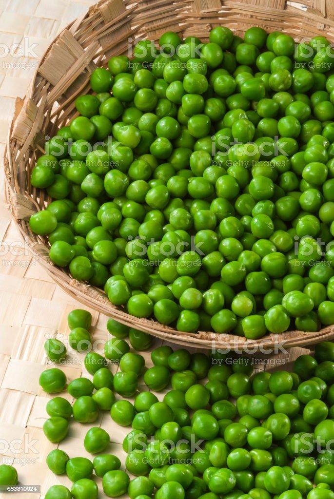 Green Peas in wooden bamboo basket royaltyfri bildbanksbilder