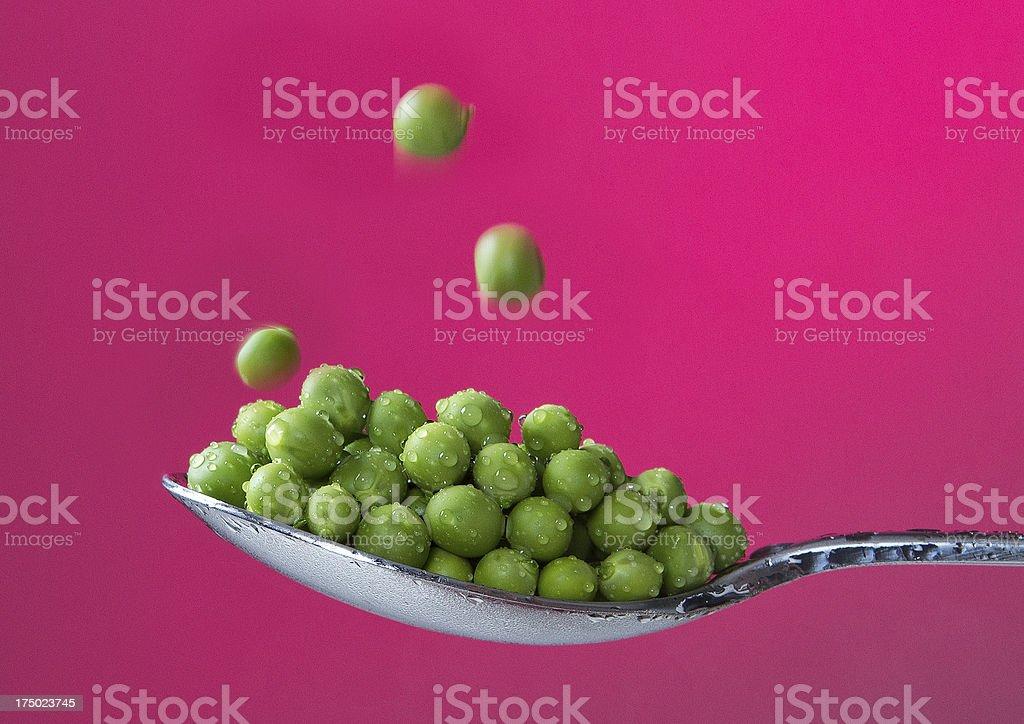 Green peas on a spoon stock photo