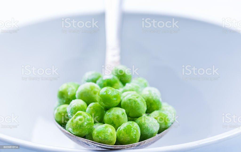 Green peas on white plate. stock photo