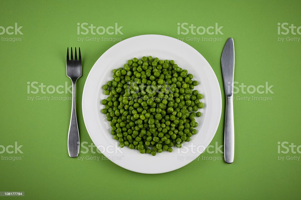 Green Peas on White Plate with Fork and Knife stock photo
