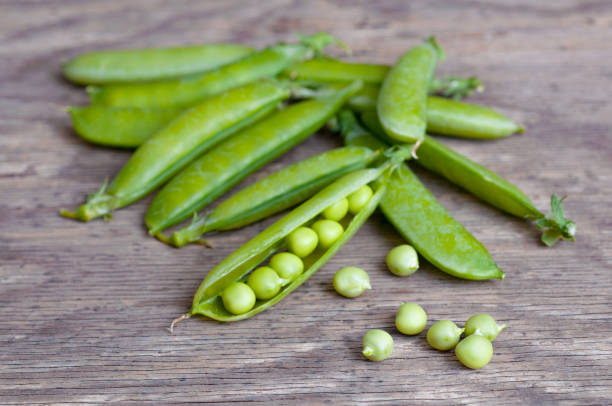 Green peas on wooden background stock photo