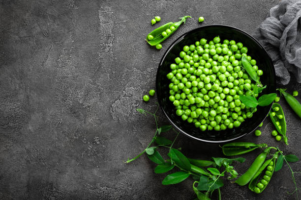 Green peas with pods and leaves stock photo
