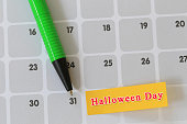 Green pen point to day 31 on calendar paper and have halloween text.