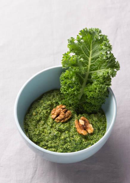 Grünes Pesto Grünkohl, Walnüsse, Knoblauch und Olivenöl auf einem grauen Hintergrund – Foto