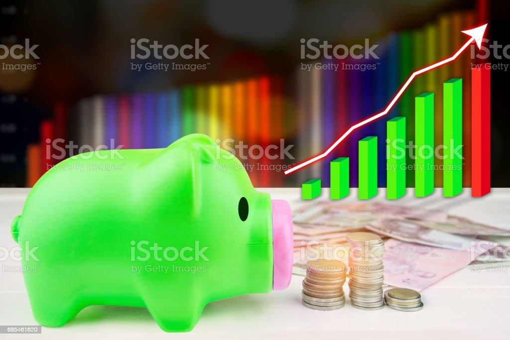Green pig piggy bank with coins and graph foto de stock royalty-free
