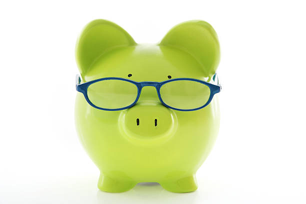 A green piggy bank wearing glasses stock photo