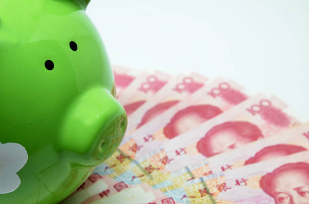 green piggy bank with china currency - disbursement stock pictures, royalty-free photos & images
