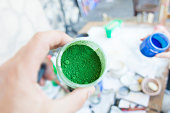 woman holding green pigment powder for painting