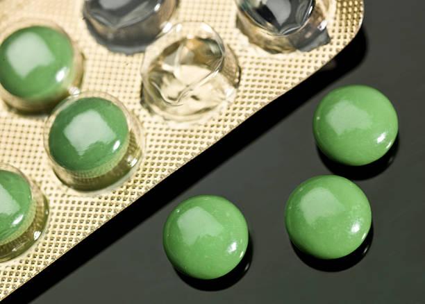 green tabletten aus seiner blisterpackung - grüner tee kapseln stock-fotos und bilder