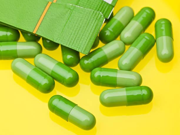 green details - grüner tee kapseln stock-fotos und bilder