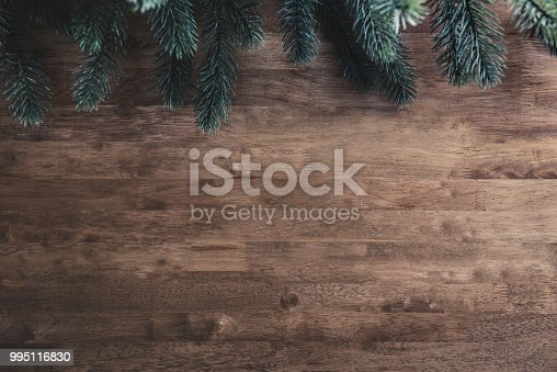 Green pine leaves on wood table, border design Christmas background with copy space