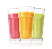 Green, pink and yellow smoothies in glasses isolated on white background
